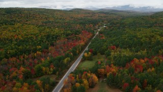 AX150_127 - 6K stock footage aerial video flying over Maine Street, rural homes, forest, approach small town, Stoneham, Maine