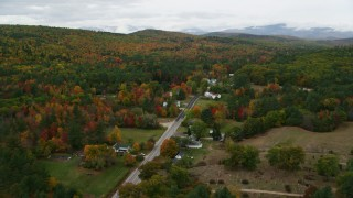 AX150_128 - 6K stock footage aerial video flying over small town rural homes, Maine Street, trees, autumn, Stoneham, Maine