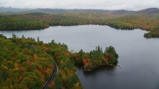 AX150_132 - 6K stock footage aerial video flying by Keewaydin Lake, colorful forest, autumn, overcast, Stoneham, Maine