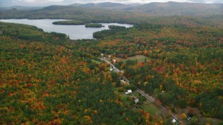 AX150_137 - 6K stock footage aerial video flying over forest, approach Cezar Lake, tilt down on rural homes, autumn, overcast, Lovell, Maine
