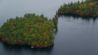 AX150_140 - 6K stock footage aerial video flying by waterfront home on forested Sheep Island, Kezar Lake in autumn, Lovell, Maine