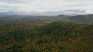 AX150_141 - 6K stock footage aerial video flying over Peaked Hill, colorful forest, approach White Mountains, autumn, Lovell, Maine