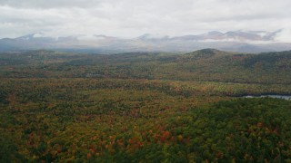 AX150_142 - 6K stock footage aerial video flying over dense forest, approaching White Mountains in autumn, Lovell, Maine