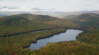 AX150_143 - 6K stock footage aerial video flying by Horseshoe Pond, dense forest, hills, autumn, overcast, Lovell, Maine