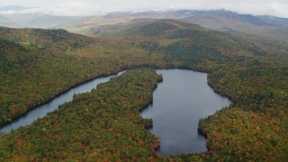 AX150_144 - 6K stock footage aerial video flying by Horseshoe Pond surrounded by dense forest, autumn, Lovell, Maine