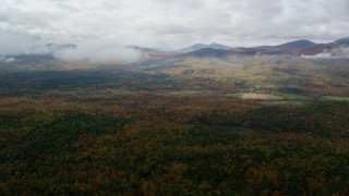 AX150_145 - 6K stock footage aerial video flying over colorful forest, approach White Mountains, cloudy, autumn, Stow, Maine