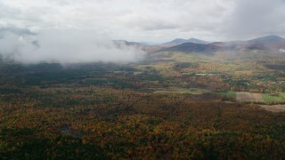 AX150_146 - 6K stock footage aerial video approaching White Mountains from over forest, autumn, cloudy, Stow, Maine