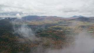 AX150_147 - 6K stock footage aerial video flying over forest, through clouds, reveal White Mountains, autumn, New Hampshire