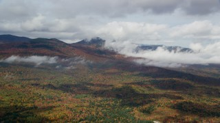AX150_149 - 6K stock footage aerial video flying over colorful forest, autumn, by clouds, White Mountains, New Hampshire