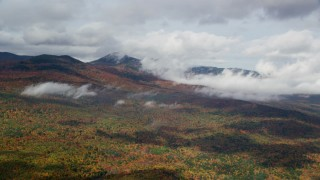 AX150_150 - 6K stock footage aerial video flying by colorful forest, autumn, cloudy, White Mountains, New Hampshire