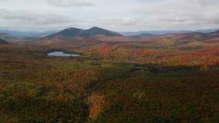 AX150_152 - 6K stock footage aerial video flying over forest, cloudy, autumn, approach Mountain Pond, White Mountains, New Hampshire