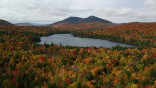 AX150_154 - 6K stock footage aerial video flying low over forest, autumn, approach Mountain Pond, White Mountains, New Hampshire