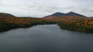 AX150_155 - 6K stock footage aerial video flying low over Mountain Pond, forest in autumn, approach White Mountains, New Hampshire