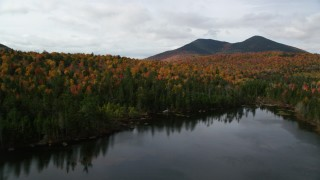 AX150_156 - 6K stock footage aerial video flying low over Mountain Pond, bright forest, approach White Mountains, New Hampshire