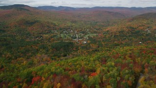 AX150_170 - 6K stock footage aerial video flying over bright forest, approaching small town of Jackson, New Hampshire