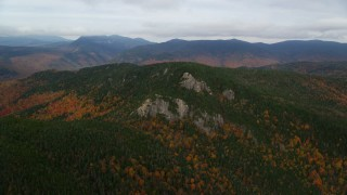 AX150_192 - 6K stock footage aerial video flying by forest, Stairs Mountain, overcast, autumn, White Mountains, New Hampshire