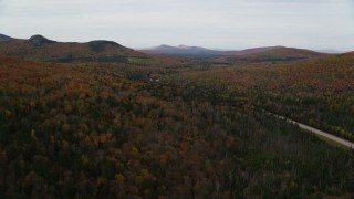 AX150_213 - 6K stock footage aerial video flying over forest, approach Highway 302, autumn, overcast, Carroll, New Hampshire