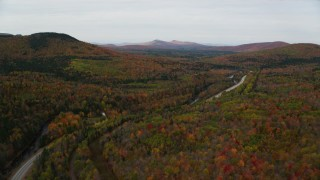 AX150_215 - 6K stock footage aerial video flying over Highway 302, tilt down on forest, autumn, Carroll, New Hampshire