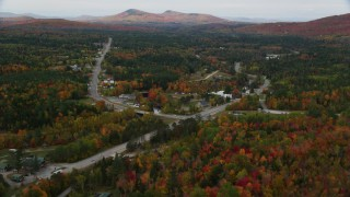 AX150_218 - 6K stock footage aerial video flying over Highway 302, approach small rural town, autumn, Carroll, New Hampshire