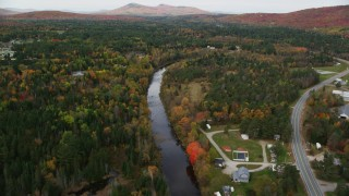 AX150_220 - 6K stock footage aerial video flying over small rural town, Ammonoosuc River, autumn, Carroll, New Hampshire