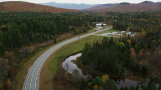 AX150_222 - 6K stock footage aerial video flying by Highway 302, North Hampshire Department of Safety, autumn, Carroll, New Hampshire