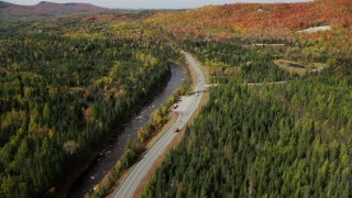 AX150_226 - 6K stock footage aerial video of Highway 302 along Ammonoosuc River, forests in autumn, Carroll, New Hampshire