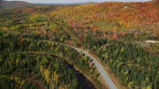 AX150_227 - 6K stock footage aerial video flying over Highway 302, Ammonoosuc River, rural homes, forest, autumn, Carroll, New Hampshire