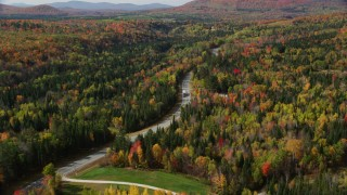 AX150_228 - 6K stock footage aerial video flying over Highway 302 through forest, rural homes, autumn, Carroll, New Hampshire