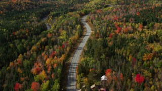 AX150_229 - 6K stock footage aerial video flying over Highway 302, brightly colored forest, autumn, Carroll, New Hampshire