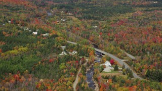 AX150_232 - 6K stock footage aerial video flying by Main Street, rural homes, Ammonoosuc River, autumn, Bethlehem, New Hampshire