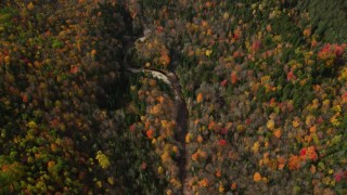 AX150_237 - 6K stock footage aerial video of a bird's eye view over forest surrounding river in autumn, Bethlehem, New Hampshire