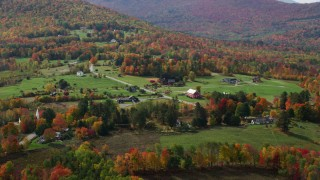 AX150_244 - 6K stock footage aerial video flying by rural homes, colorful trees in autumn, Sugar Hill, New Hampshire