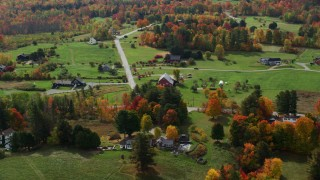 AX150_245 - 6K stock footage aerial video flying by brightly colored trees, rural homes in autumn, Sugar Hill, New Hampshire