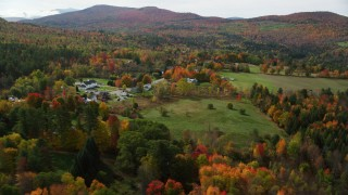 AX150_247 - 6K stock footage aerial video flying by colorful trees, rural homes, small rural town, autumn, Sugar Hill, New Hampshire
