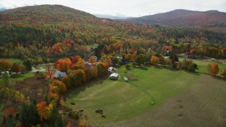 AX150_248 - 6K stock footage aerial video orbiting a small rural town, colorful trees in autumn, Sugar Hill, New Hampshire
