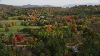 AX150_250 - 6K stock footage aerial video flying away from small rural town, by colorful trees, autumn, Sugar Hill, New Hampshire