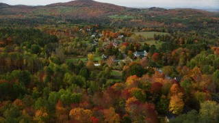 AX150_255 - 6K stock footage aerial video approaching a small rural town, colorful foliage in autumn, Sugar Hill, New Hampshire