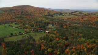 AX150_257 - 6K stock footage aerial video approaching Pearl Lake Road, tilt down over rural homes, pond, autumn, Lisbon, New Hampshire