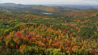 AX150_259 - 6K stock footage aerial video flying over colorful forest, approaching Pearl Lake, autumn, Lisbon, New Hampshire