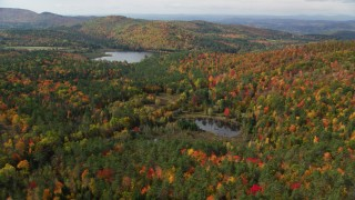 AX150_260 - 6K stock footage aerial video flying over a forest, approaching Pearl Lake, autumn, Lisbon, New Hampshire