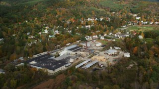 AX150_265 - 6K stock footage aerial video flying by a factory near river, small town, autumn, Lisbon, New Hampshire