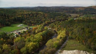AX150_266 - 6K stock footage aerial video flying over rural homes, Ammonoosuc River, autumn, Lisbon, New Hampshire