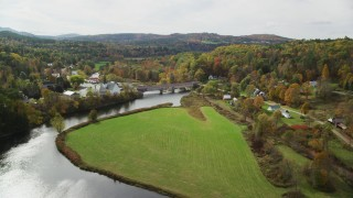AX150_272 - 6K stock footage aerial video flying over Ammonoosuc River, grassy clearing, approach rural town, Bath, New Hampshire