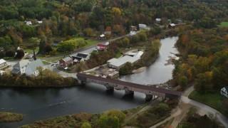 AX150_273 - 6K stock footage aerial video orbiting rural town, covered bridge, church, Ammonoosuc River, autumn, Bath, New Hampshire