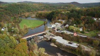 AX150_274 - 6K stock footage aerial video orbiting small rural town, Ammonoosuc River, bridge, church, autumn, Bath, New Hampshire