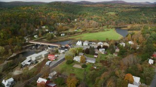 AX150_275 - 6K stock footage aerial video orbiting a real town on the Ammonoosic River, in autumn, Bath, New Hampshire