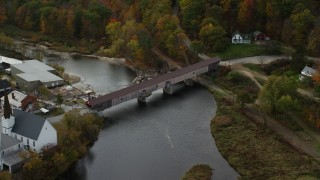AX150_276 - 6K stock footage aerial video orbiting bridge spanning Ammonoosuc River, rural town, autumn, Bath, New Hampshire