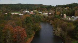 AX150_279 - 6K stock footage aerial video flying over Ammonoosuc River through small town, approach bridge, autumn, Bath, New Hampshire