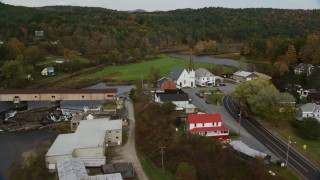 AX150_280 - 6K stock footage aerial video approaching bridge, tilt down over church, Ammonoosuc River, autumn, Bath, New Hampshire