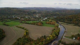 AX150_283 - 6K stock footage aerial video flying over small farms Ammonoosuc River, approach rural town, autumn, Woodsville, New Hampshire
